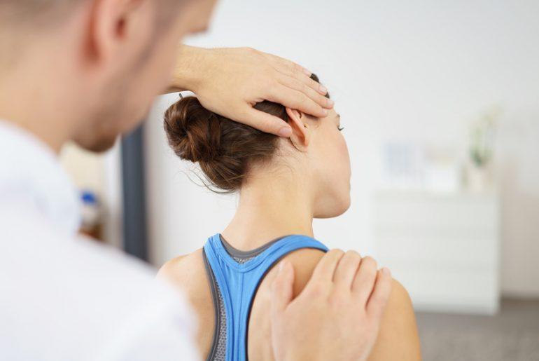 Physiotherapeut behandelt eine Patientin mit Nackenschmerzen /  contrastwerkstatt / Fotolia.com