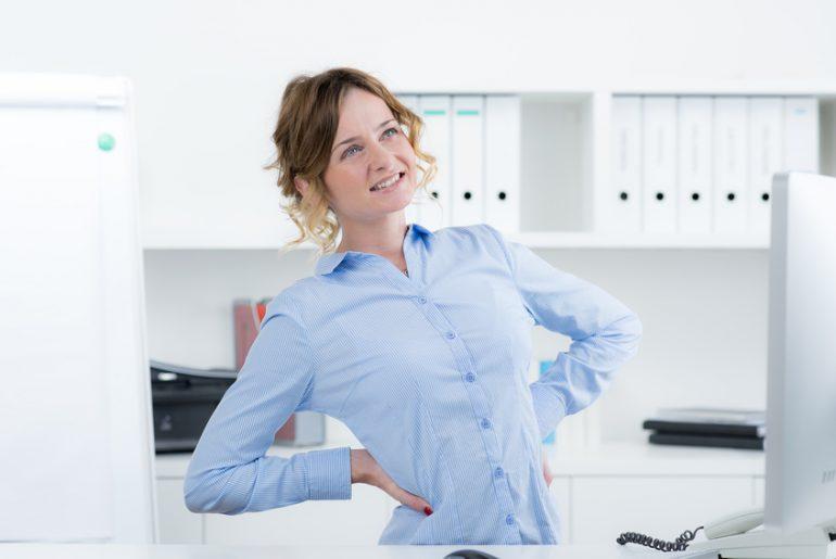 frau hat rückenschmerzen von falscher haltung