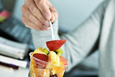 Mann isst Fruchtsalat im Büro
